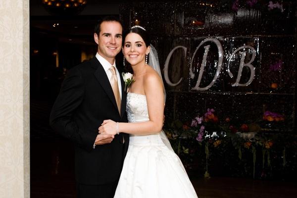 Bride and groom in front of monogram ice sculpture