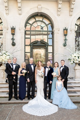 bride in pnina tornai wedding dress with groom, bridal party, and parents