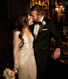 Bride in long sleeve Inbal Dror wedding dress with groom in tuxedo bow tie with long brunette hair