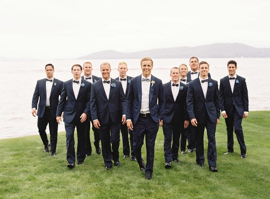 Groom in navy tuxedo with grey bow tie with groomsmen in bow ties by lake in New Hampshire