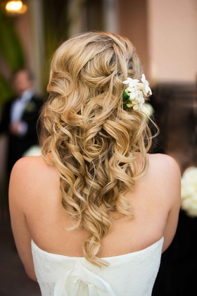 Blonde bride with curled long hairstyle with stephanotis blossoms in hair