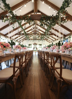 Wedding with wood floor, greenery hanging from rafters, pink centerpiece, moss candelabra