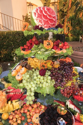elaborate and luxurious tower of fruit with cascading grapes and carved watermelon at cocktail hour