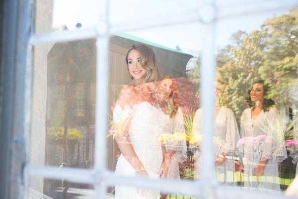 Wedding getting ready bridal suite bride in anne barge wedding dress bridesmaids through window