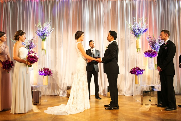 bride in allure bridals gown, groom in burberry, wedding ceremony with blue and purple flowers