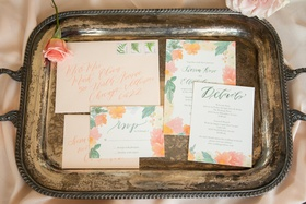 peach envelopes and floral invitation suites with pink orange and greenery