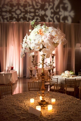 Wedding reception centerpiece of golden candelabra with white orchids, orange roses, and hydrangeas