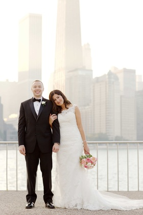 Groom in tuxedo with bow tie and bride in wedding dress pink bouquet in front of Chicago skyline