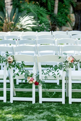 white ceremony chairs draped with rose and greenery garland