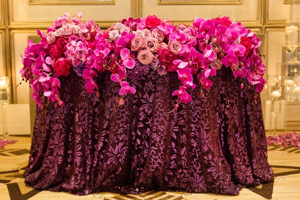 pink and purple floral arrangements orchids roses linens reception cascading