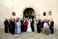 Bride and groom with guests in front of church