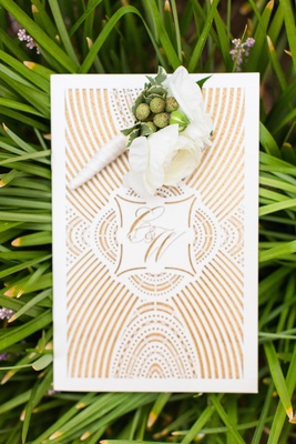 White and green berry boutonniere on top of wedding invite