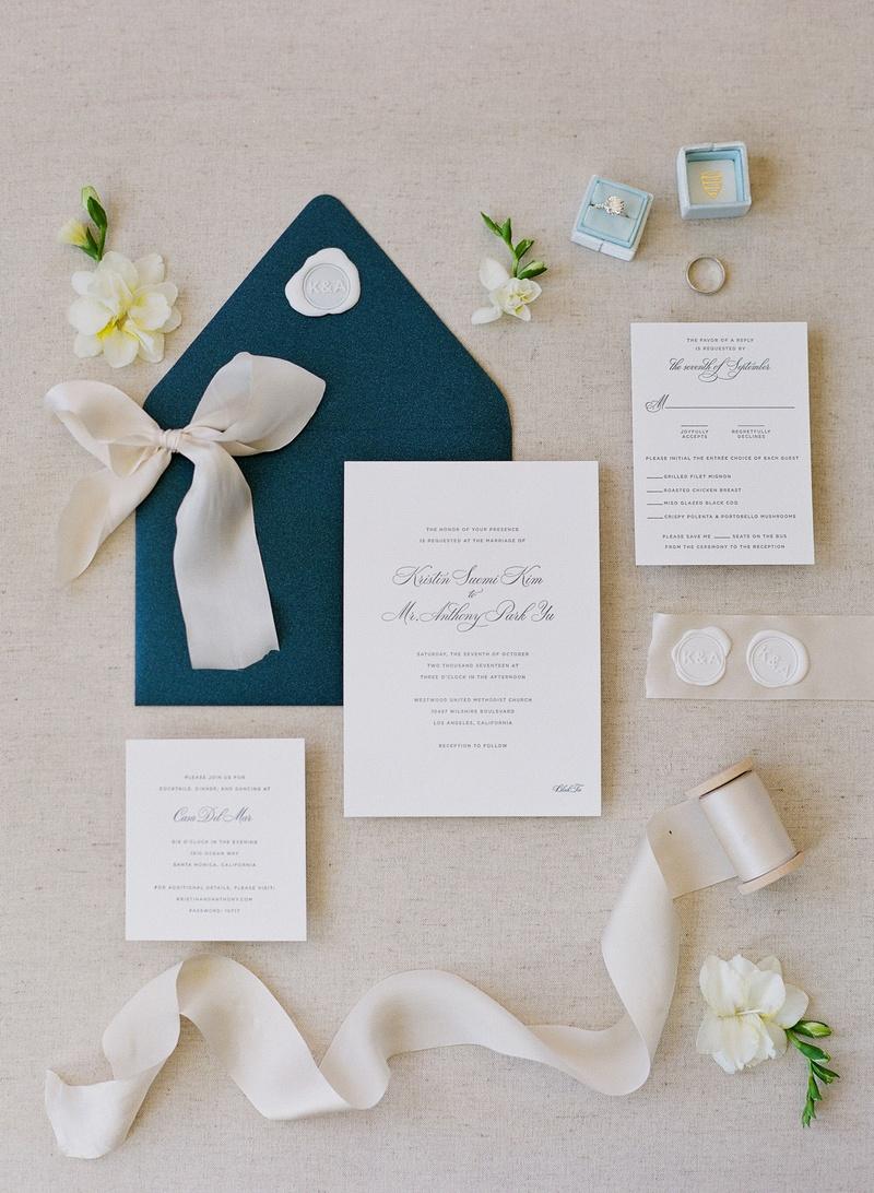 pretty wedding invitation navy blue envelope wax seal calligraphy light blue velvet ring box ribbon