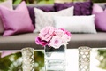 pink and purple floral arrangements roses in glass vase on mirror table ceremony