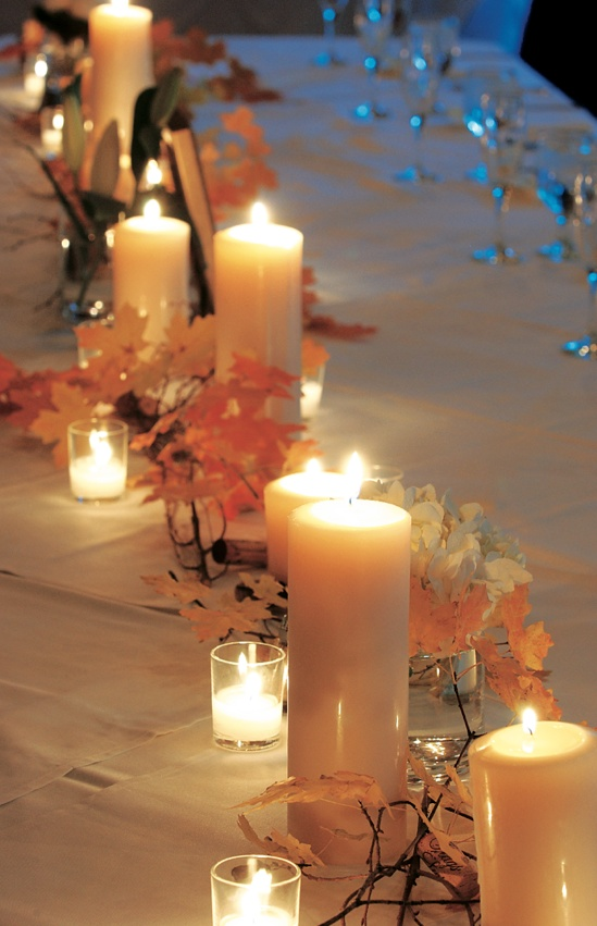 White pillar candles and autumn leaves on guest table