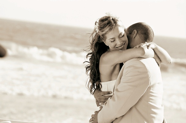 Bride and groom hug on beach near ocean