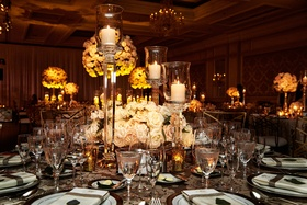 Wedding reception low rose centerpiece flowers with candles in tall candlesticks