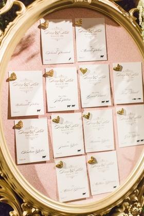 Gold frame pink bulletin board gold heart pins escort cards wedding idea
