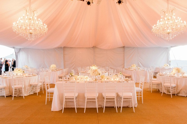 Beach tented wedding reception with crystal chandeliers, white linens, chairs, flowers, burnt orange
