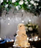 wedding cake on silver stand buttercream stripes white pink rose flowers greenery