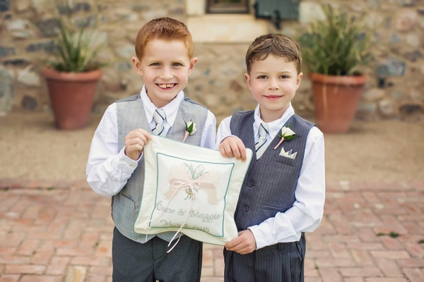 Ring bearers in vest striped tie boutonniere holding needlepoint embroidery ring pillow