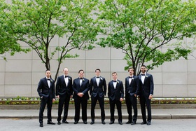 groom and groomsmen tuxedos bow tie white boutonniere flowers