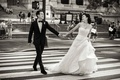 Black and white photo of Chinese American bride and groom in crosswalk of New York City street