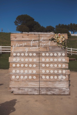 Circle escort cards on rustic wood board with calligraphy please find your seat and flowers