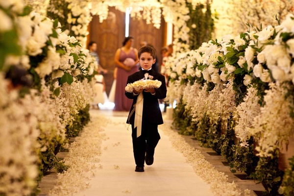 Little boy walking down floral-embellished aisle
