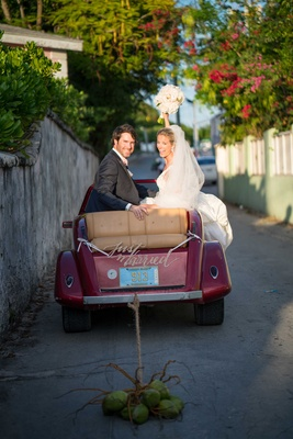 Bride and groom in just married car red vehicle with Bahamas license plate coconuts instead of cans