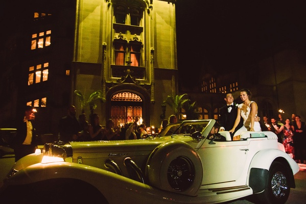 Wedding send off grand exit bride and groom sitting on back of classic car outside of venue wedding