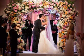 Bride in strapless Vera Wang wedding dress kissing groom under flower chuppah at Jewish wedding