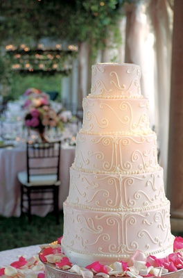 Five layer cake with pale pink frosting and petals