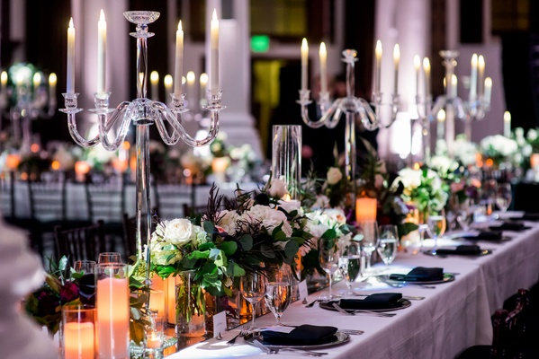 Long wedding reception tables with crystal candelabra greenery white flowers feathers black napkins