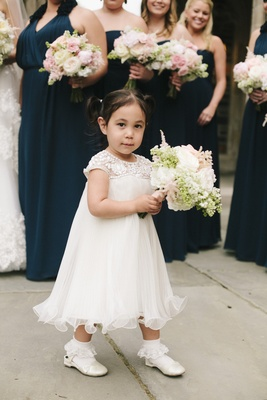 Flower girl holding large bouquet in beaded white dress