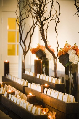 Fall wedding escort cards on branch and wood table