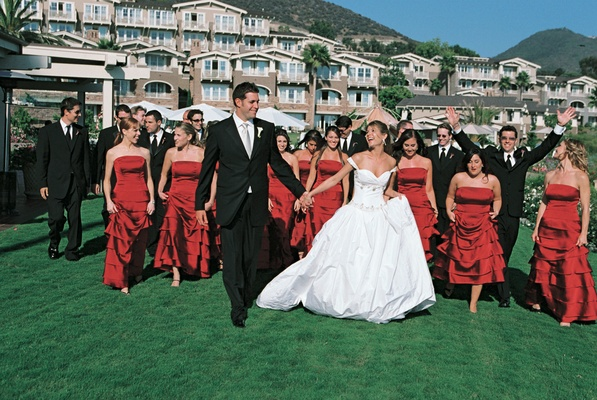 bridesmaids wearing red dresses walk with groomsmen and newlyweds