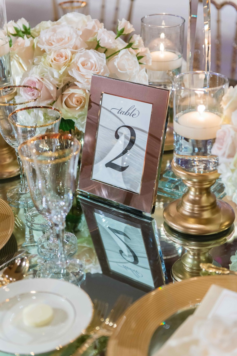 Framed table number on mirror reception table with gold candle holder floating candles rimmed glasse