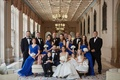 Bride in Anne Barge wedding dress, groom and groomsmen in tuxedos, bridesmaids bright blue dresses