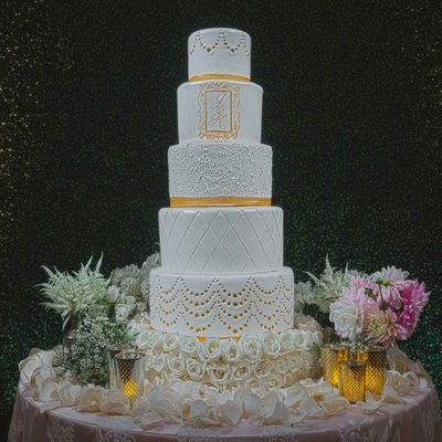 White and gold wedding cake five layers with different designs and monogram