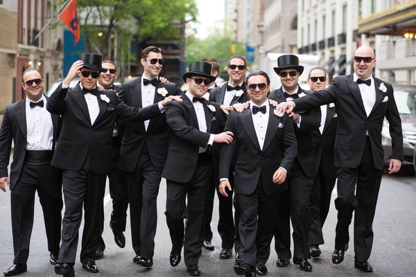 Groom with friends in tuxedos and top hats