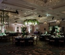 ballroom wedding reception round rectangular tables greenery white flowers candelabra ceiling decor