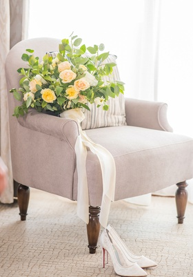 wedding bouquet on chair at bacara santa barbara greenery yellow rose peach white flowers ribbon