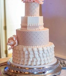 Wedding cake with with white and pastel pink layers, quilted and pearl dot pattern, ruffles
