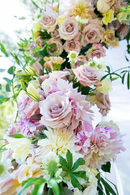 flowers in shades of blush, ivory, and off-white with greenery clinging to couples outdoor chuppah