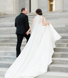 bride in justin alexander plain ball gown, holds train walks up steps with groom