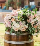 Wedding ceremony outdoor Sergio Garcia golfer wood barrel with fresh flowers on top