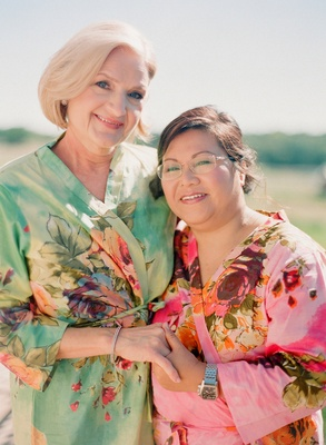 Mother of the bride and mother of the groom wear floral aqua and pink robes