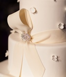 White wedding cake with top golden layer, fondant ribbon, and rhinestone pin, small fondant flowers