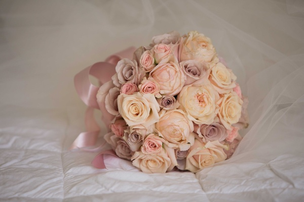 Ivory rose, pink rose, light lavender purple rose flowers in bridesmaid bouquet with pink ribbon